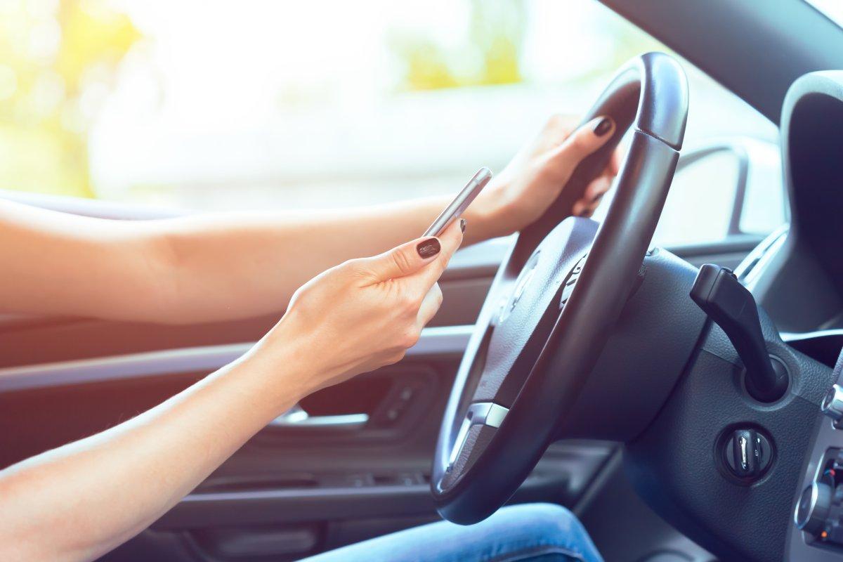 jedna ręka na kierownicy a druga trzyma telefon